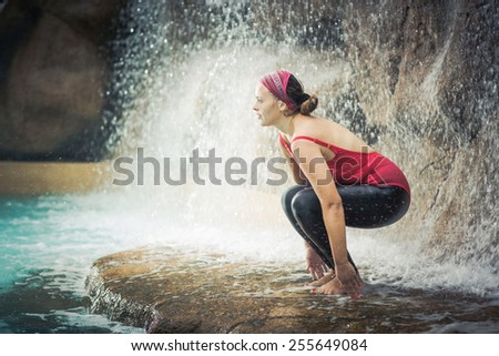Woman practicing yoga near waterfall. Awkward Pose. Utkatasana - stock photo
