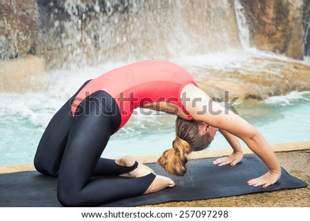 Woman practicing yoga near waterfall. Extended Camel Pose. Utthita Ustrasana - stock photo