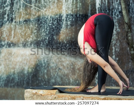 Woman practicing yoga near waterfall. Standing Forward Bend. Uttanasana - stock photo