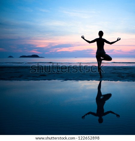 Woman practicing yoga on the beach after sunset - stock photo