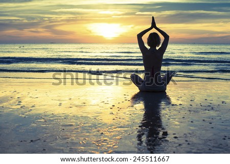 Woman practicing yoga on the beach at sunset in Thailand.