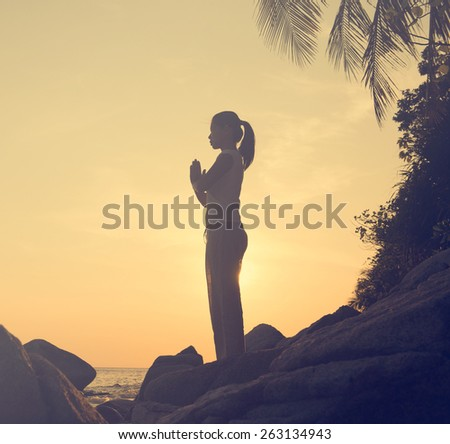 Woman practicing yoga on the beach at sunset, vintage tone