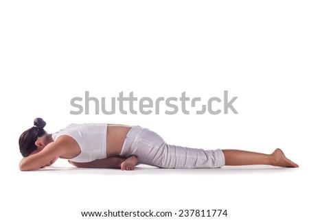 Woman practicing yoga preparing for Eka Pada Rajakapotasana against white background. - stock photo