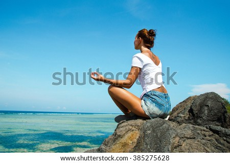 Woman Practicing Yoga sitting on a rock in front of the azure ocean. Stock image