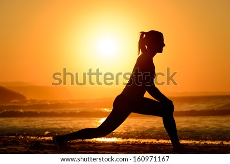 Woman practicing yoga, stretching and relaxing exercises on the beach at sunset. Female athlete silhouette exercising on towards the sea on bright golden sun background.