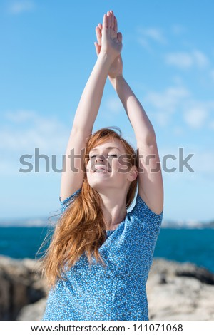 Woman practising yoga at the sea standing on a rocky coastline with her arms raised and a serene expression