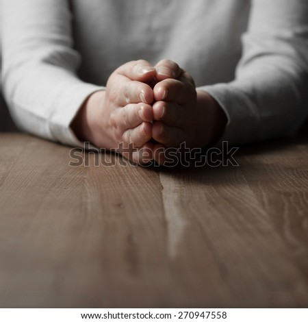 woman praying hands on wooden background - stock photo