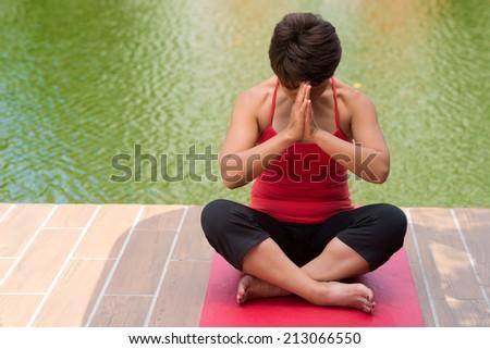 Woman praying in lotus position - stock photo