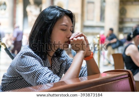 Woman praying in the church. Believers meditates in the cathedral. Spiritual time of prayer.  - stock photo