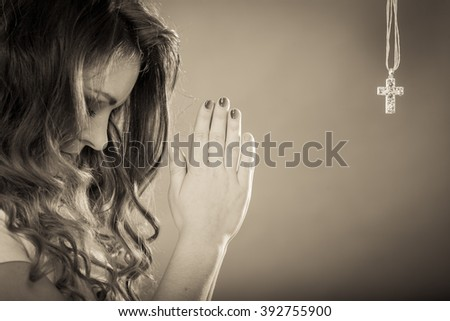 Woman praying to god jesus christ with cross necklace pendant. Strong christian religion faith. Christianity. - stock photo