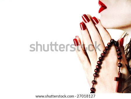Woman praying with rosary - stock photo