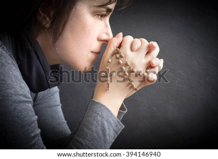woman praying with rosary in her hand - stock photo