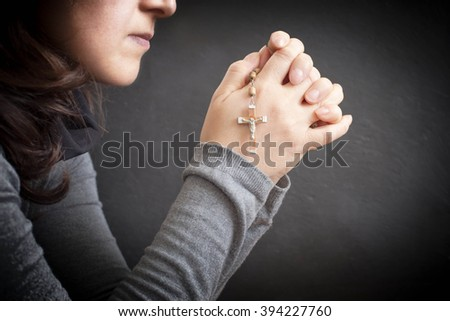 woman praying with rosary in her hand