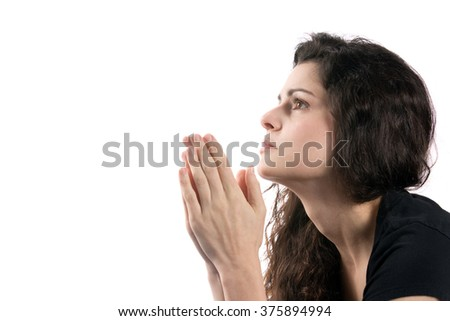 Woman prays while looking up with her hands together. - stock photo