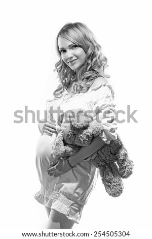 woman pregnant on white background with toy. Black and white - stock photo