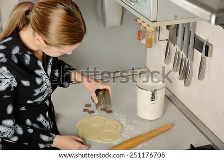Woman prepare dough on the table in the kitchen - stock photo
