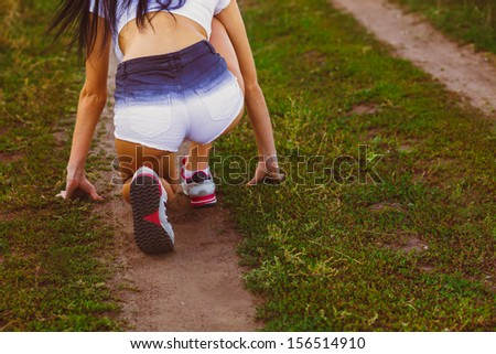 woman prepared to run a rear view ass and sneakers close up, playing sports outdoors