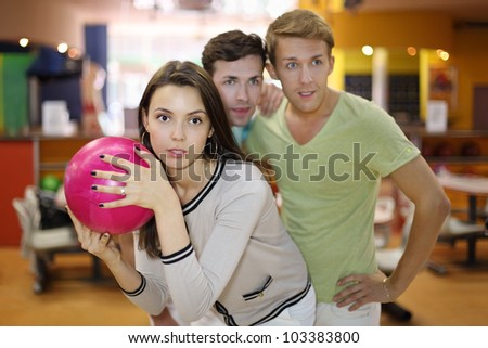 Woman prepares to throw of pink ball in bowling; two men look at aim; focus on woman; shallow depth of field - stock photo