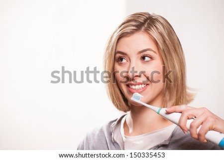 Woman prepares to use an electric toothbrush.