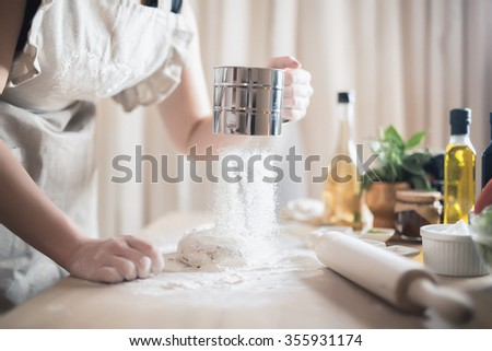 Woman preparing dough basis.Ingredients for baking.Female hands spilling powder on dough.Making dough by female hands.Cooking and baking concept - stock photo