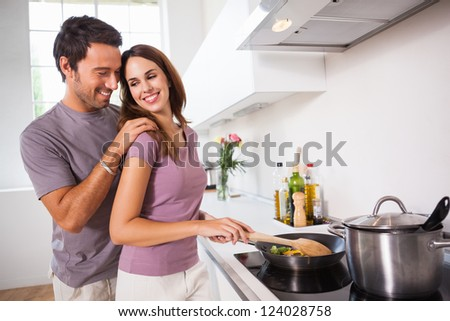 Woman preparing food at the stove with partner behind her in kitchen