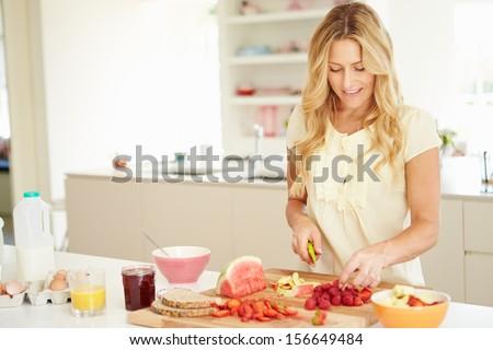 Woman Preparing Healthy Breakfast In Kitchen - stock photo