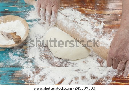 Woman pressing dough with rolling pin. Woman rolling dough with rolling pin on kitchen counter - stock photo