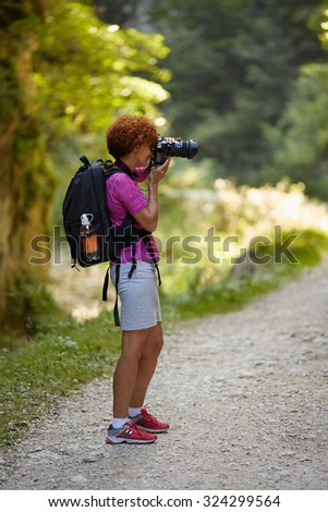 Woman professional nature photographer taking photos outdoor - stock photo