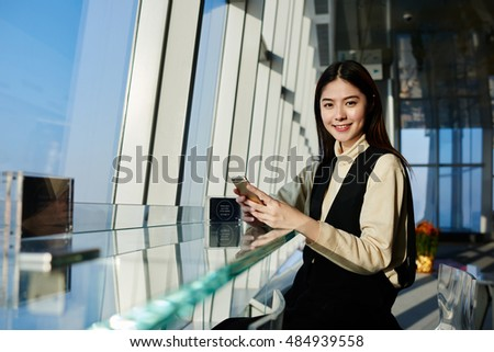 Woman professional specialist in the economic sphere is using mobile phone before the interview with the managing director of successful company in China, while is sitting inside skyscraper building