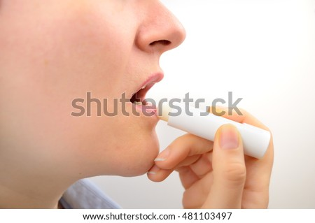 woman profile putting balsam lips to repair her lips of the causes of winter cold in white background