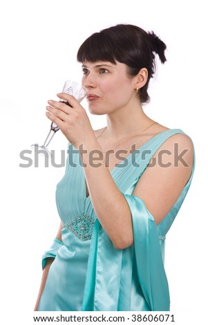 Woman proposes a toast to smb's health. Girl in greenness of the sea dress is standing and holding a glass of wine.