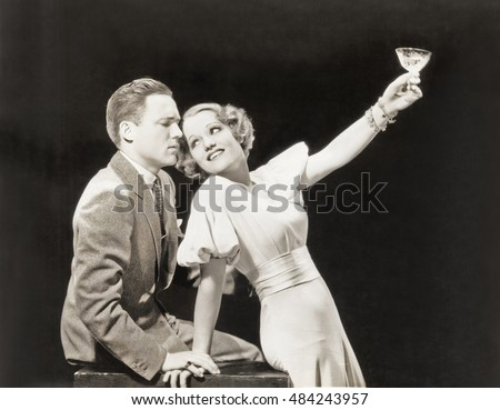 Woman proposing a toast to hesitant man