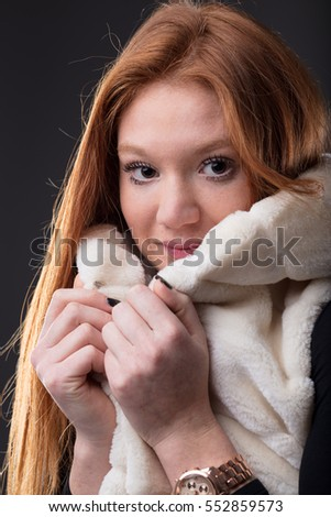 woman protecting herself from cold holding a white fur soft scarf