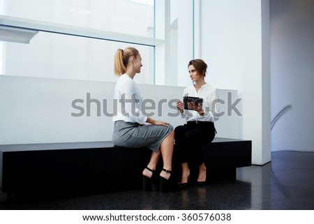 Woman proud ceo with touch pad conducting interview with charming and smart female while sitting in office interior, two business partners discussing project on digital tablet during meeting in hall - stock photo
