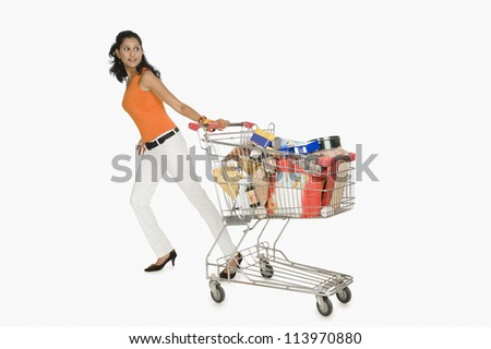 Woman pulling a shopping cart and smiling - stock photo