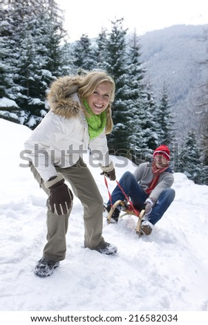 Woman pulling boyfriend on sled on remote snowy hillside