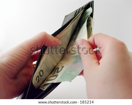 Woman pulling money out of a wallet - stock photo
