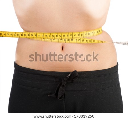 woman pulling on tape measure around her waist to get as slim as possible. Extreme diet concept - stock photo