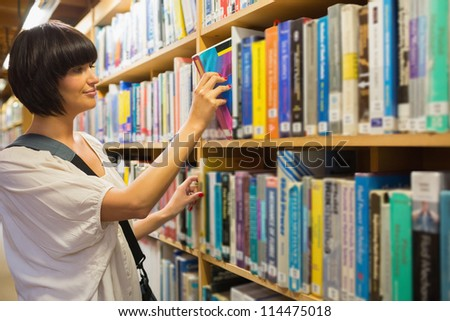 Woman pulling out a book from a shelf in the library - stock photo