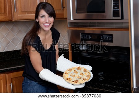 Woman pulling pie from oven - stock photo