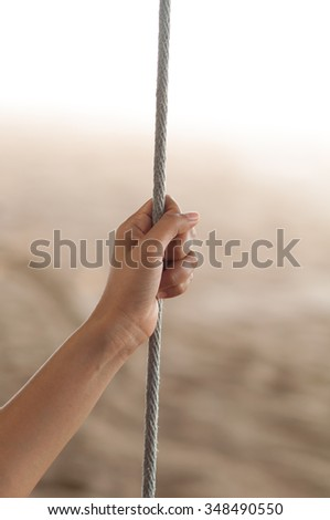 woman pulling the rope with one hand - stock photo