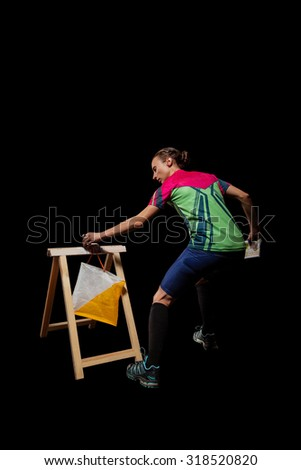 Woman punching at control point, taking part in orienteering competitions. Isolated on black. File contains clipping path - stock photo
