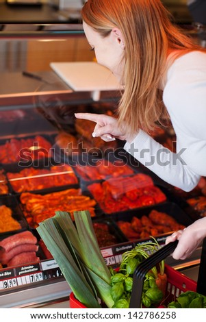 Woman purchasing meat at a delicatessen leaning forwards pointing to her selection behind a glass counter display - stock photo