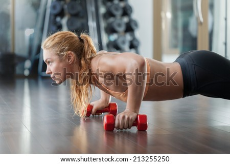 Woman push-ups on the floor - stock photo