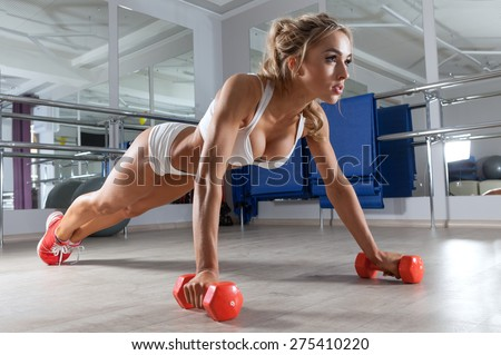 Woman push-ups on the floor at the gym - stock photo