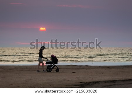 Woman pushing a baby stroller on a beach in the sunset light - stock photo