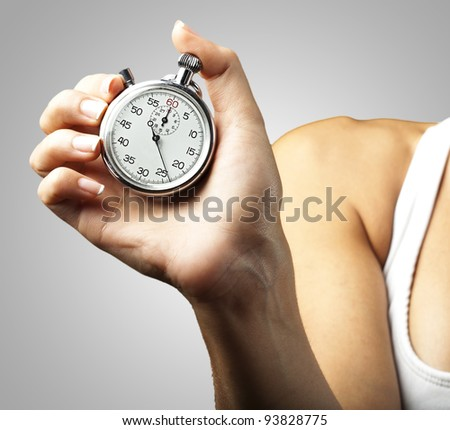 woman pushing a stopwatch button against a grey background - stock photo