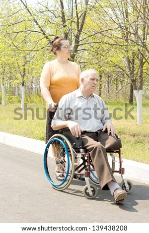 Woman pushing senior man in wheelchair in the park - stock photo