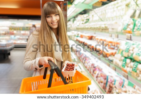 Woman put berries to basket at supermarket