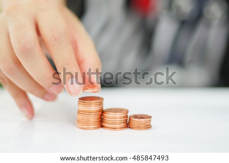 Woman put coins to stack of coins, Collecting and Saving Money background concept